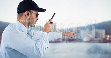Security guard with walkie talkie pointing against blurry skyline