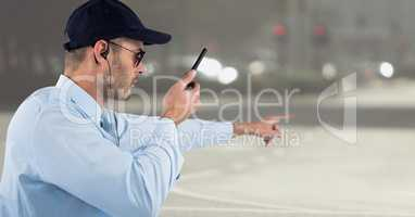 Security guard with walkie talkie pointing against blurry street