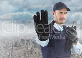 Security guard with walkie talkie and hand up against skyline and clouds
