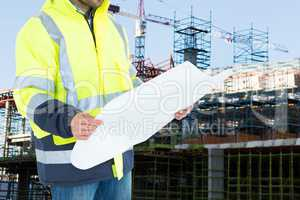 Engineer watching plans on construction site