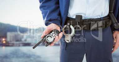 Security guard lower body with walkie talkie against blurry skyline