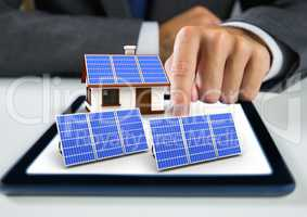 solar panel and house with solar panel on tablet with businessman hand