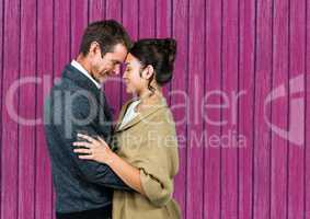 couple huging and looking each other with pink wood background