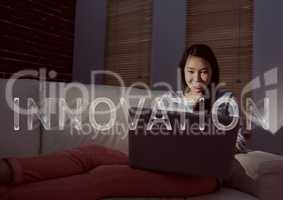 White innovation text and woman on couch with laptop