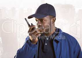 Security guard with walkie talkie against faded skyline