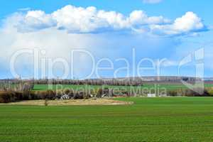 Rural landscape with a green field, clouds and farm