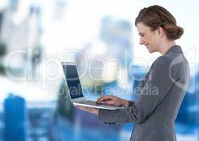 Businesswoman holding laptop in blue motion public space