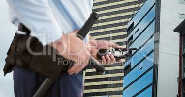 Mid section of security guard holding baton and walkie talkie standing against buildings