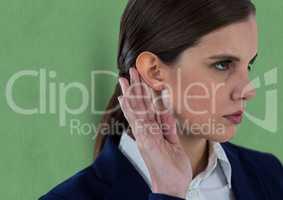 Businesswoman listening gossip while standing against green background