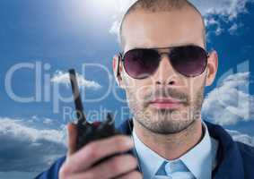 Security guard holding walkie talkie during sunny day