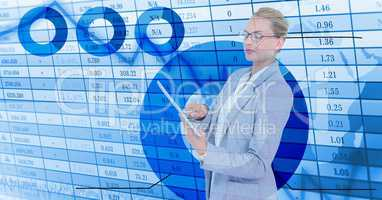 Businesswoman holding digital tablet standing by numerical background