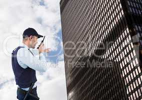 Security guard talking on walkie talkie while pointing towards building