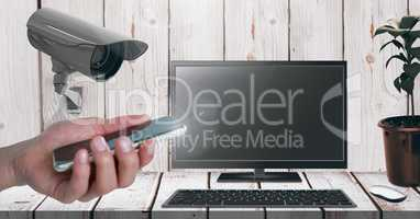 Hand holding mobile phone with Security camera watching laptop