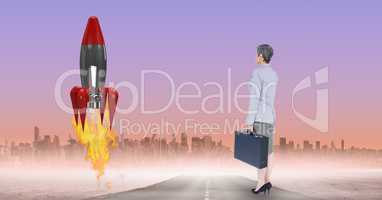 Digital composite image of businesswoman watching rocket launch against city