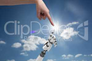human hand is touching robot hand against sky background