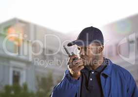 security guard speaking with the walkie-talkie in front of a building