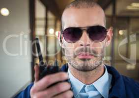 security guard with glasses, headphone and walkie-talkie in the office