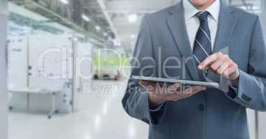 Businessman holding tablet in long room space