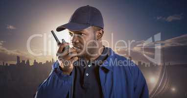 Security guard with walkie talkie against skyline and sunset