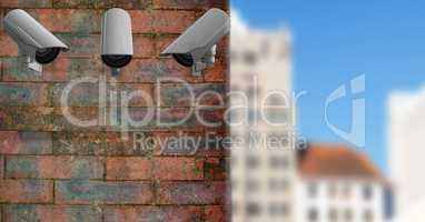 3 CCTV on a brick wall with the city in the background