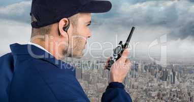 Security guard with cap and walkie talkie against skyline and clouds
