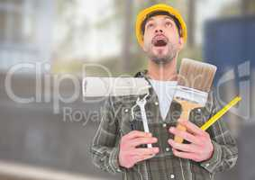 Construction Worker with paint tools in front of construction site