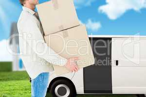 deliver is holding packages in order to load a car against garden background
