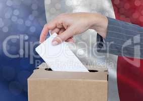 Hand putting France vote in ballot box with sparkling light bokeh background