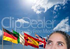 main language flags behind foreground of young woman thinking