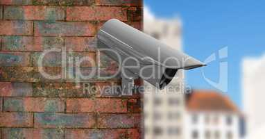 CCTV on a brick wall with the city in the foreground