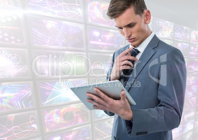 Businessman holding tablet with bright colorful screens visuals