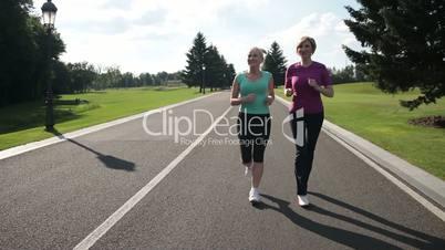 Jogging senior women running parkway in sportswear