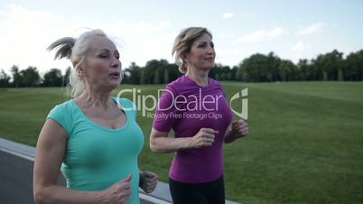 Active fit senior female athletes running outdoors