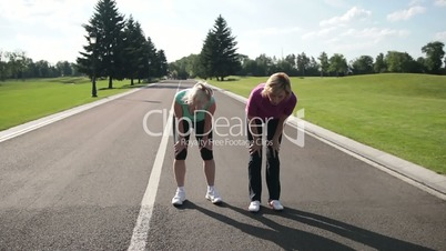 Exhausted female runners resting after jogging