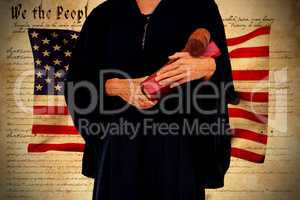 Composite image of midsection of female lawyer holding gavel and book