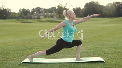 Healthy adult woman doing yoga exercises outdoors