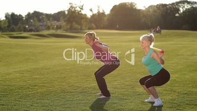 Slim adult women doing squats with bodybar in park