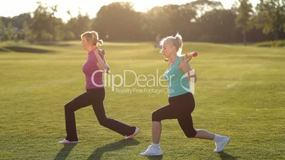 Fit adult women doing forward lunges with body bar