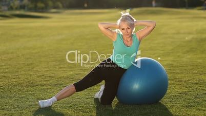 Sporty fit lady doing side crunches on ball
