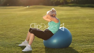 Sportswoman doing abdominal crunches on fit ball.