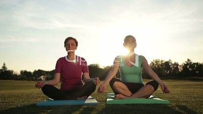 Serene women meditating in half lotus at sunset