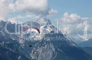 Gleitschirmflieger vor der Zugspitze in Bayern