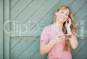 Outdoor Portrait of Young Adult Brown Eyed Woman Listening To Mu