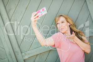 Young Adult Woman Wearing Earphones Taking a Selfie with Her Sma