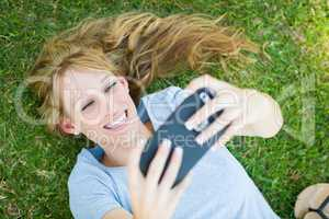 Young Adult Woman Laying in Grass Taking a Selfie with Her Smart