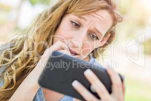 Concerned Young Woman Outdoors Looking At Her Smart Phone.