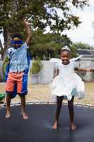 Playful siblings in costumes jumping on trampoline