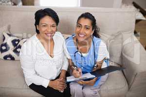 Portrait of smiling patient sitting with doctor checking medical report