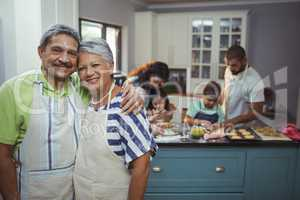 Senior couple smiling at camera while family members preparing dessert in background