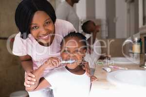 Smiling mother with daughter brushing teeth in bathroom at home